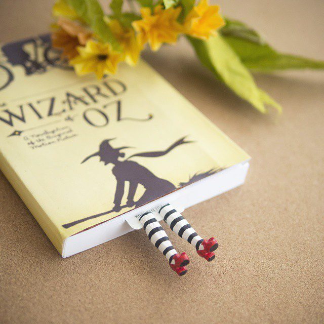 Quirky Bookmarks Look Like Tiny Legs of Literary Characters Sticking Out Between Pages 1
